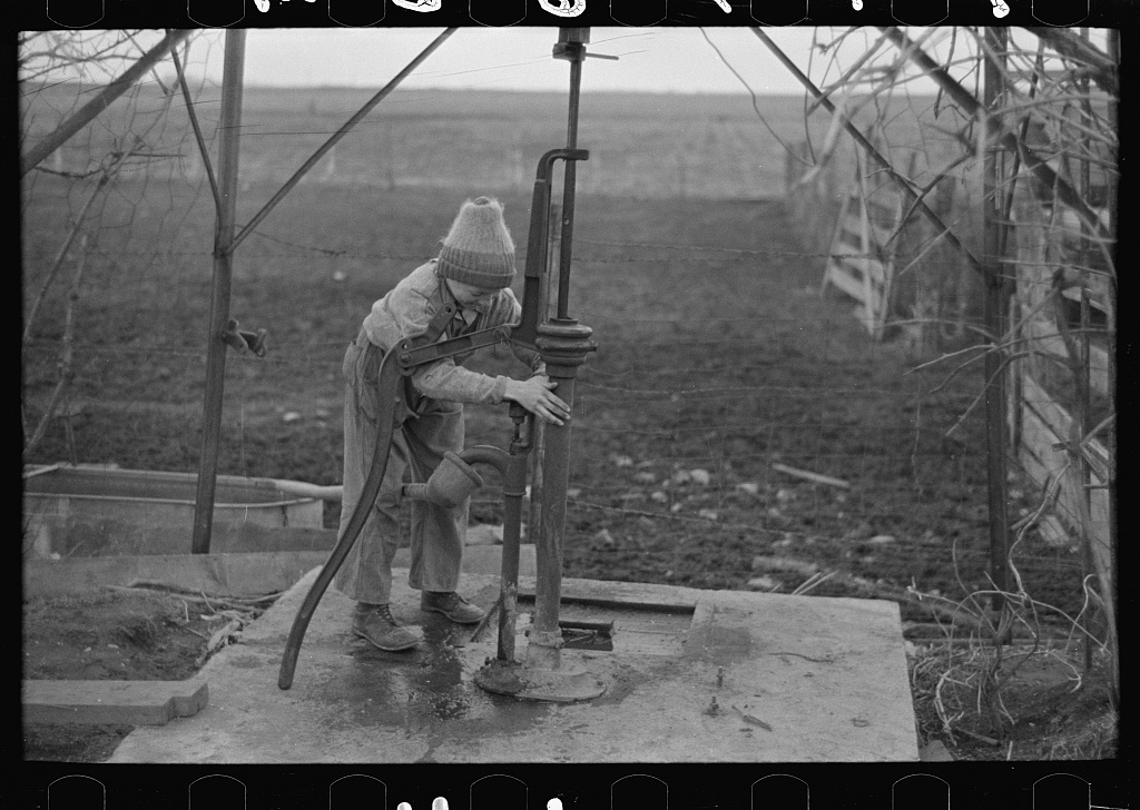 Late afternoon. One of Tip Estes' sons disconnects pipe from the windmill pump. Fowler, Indiana