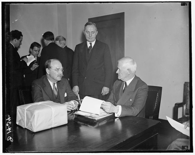 Maritime Commission opens bids for new combination passenger and cargo liner. Washington, D.C., April 1. Taking its first major step toward developing the American Merchant Fleet, the new federal maritime Commission opened bids today for the construction of a combination passenger and cargo liner to replace the S.S. Leviathan in Transatlantic service. The bids were submitted under the 1936 Merchant Marine Act which specifies that plans must include all the latest safety and National defense features. The War and Navy Departments have requested that the Leviathan be retained as a Military Auxiliary. In the photograph, left to right: Commissioner M.M. Taylor; Telfair Knight, Secretary to the Commission; and Rear Admiral H.A. Wiley, Chairman of the Commission, 4/1/1937