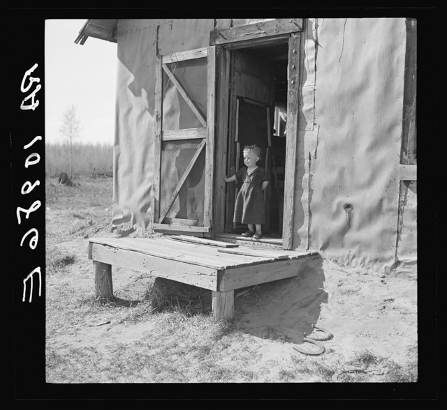 Max Sparks' youngest child standing in the doorway of his shack home near Long Lake, Wisconsin. She is a deaf mute