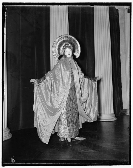 "Mrs. [...]Benda, wife of the famous ""Benda Masques,"" in a costume known as the ""The Golden Goddess."" The masque and costume are both done by Benda"