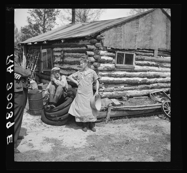 Mrs. Hale and her oldest son in front of their home near Black River Falls, Wisconsin. This farm house was built with a total expenditure of three dollars in money