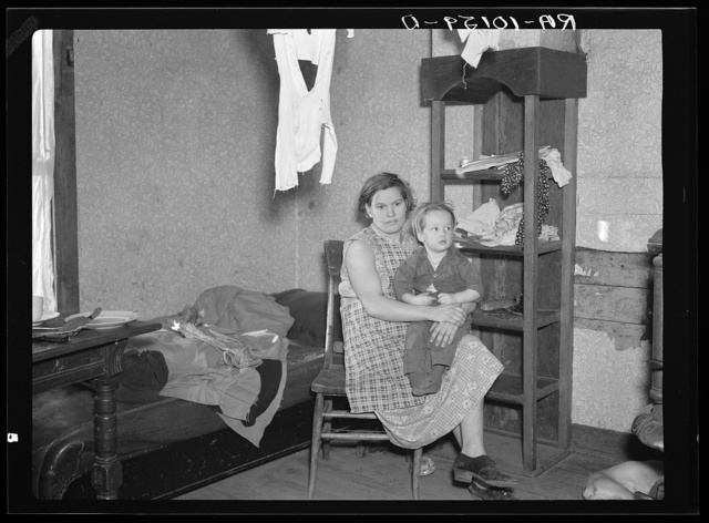 Mrs. James Kelleher, wife of a hired man, and one of her children. Except for a bed, a stove and a dresser, these are the only articles of furniture in the house. Near Grand Ridge, Illinois