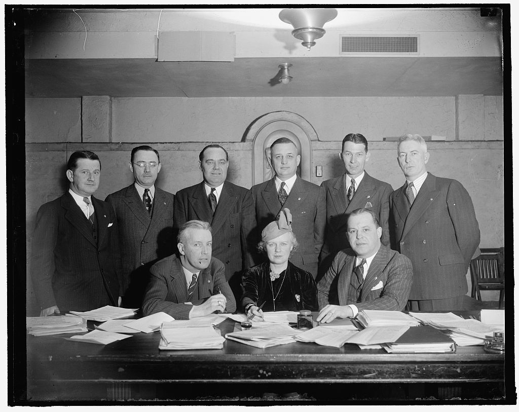 National Veteran's Employment Committee of the American Legion. Seated, L-R: Jack Crowley of Vermont, Nat'l Chairman of Vet. Emp. Comm.; Mrs. Ada Mucklestone of Ill., National Chairman of the American Legion Auxiliary; Paul H. Griffith, (D.C.), National Director of Re-Employment. Standing, L-R: [...], F. Regan of N.J.; Wm. D. Reilly of Kansas; Roy S. Stockton of California; Spencer Boise of North Dakota; James W. Hammond of Kentucky; Harold P. Redden of Massachusetts. Attending conferences at the Hamilton Hotel about securing employment for World War Veterans