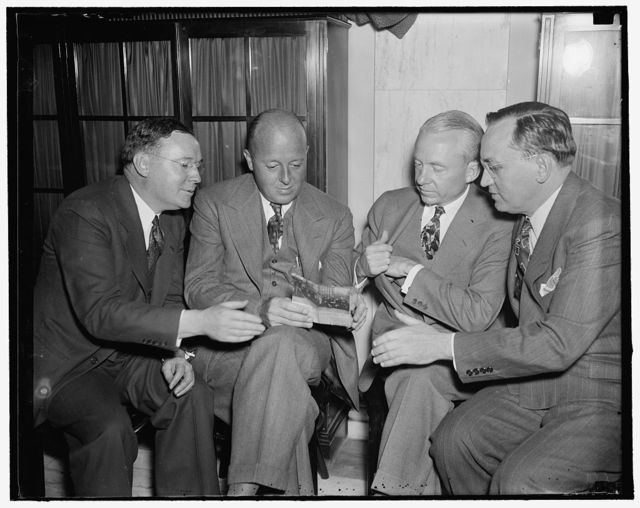 New heads of the Van Sweringen RR Empire. Washington, D.C., May 6. Senator Wheeler's Senate Committee began today started investigation of the latest transfer of control of the Van Sweringen Railroad Empire. Two weeks ago George Ball sold the control to three brokers of the New York namely Young, Kobe and Co. who are closely identified with General Motors and Du Pont interests. Left to right in a huddle before the session are: Walter S. Orr, attorney for the brokers; and the new owners Allen P. Kirby; Robert R. Young; and Frank F. Kolbe, 5/6/1937