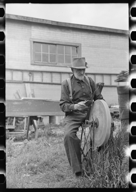 Old resident of Winton, Minnesota, sharpening an axe
