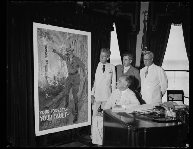 PRESIDENT ACCEPTS FIRE PREVENTION POSTER. WASHINGTON, D.C. JUNE 10. PRESIDENT ROOSEVELT TODAY ACCEPTED FOR THE GOVERNMENT THE PAINTING MADE BY JAMES MONTGOMERY FLAGG TO BE USED BY THE U.S. DEPARTMENT OF AGRICULTURE ON POSTERS THROUGHOUT THE COUNTRY. IT SHOWS UNCLE SAM AS A FOREST RANGER IN A FOREST WITH THE SLOGAN 'YOUR FORESTS--YOUR FAULT--YOUR LOSS.' L TO R: BEHIND THE PRESIDENT ARE JAMES MONTGOMERY FLAGG, THE ARTIST; SEC. OF AGRICULTURE HENRY WALLACE; EARLE H. CLAPP, CHIEF OF THE U.S. FOREST SERVICE