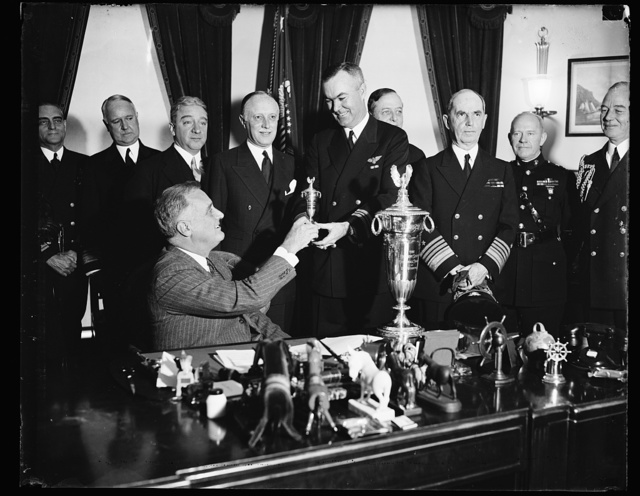 PRESIDENT AWARDS SCHIFF TROPHY, WASHINGTON, D.C. JANUARY 14. PRESIDENT ROOSEVELT PRESENTING THE SCHIFF TROPHY FOR 1936 TO COMMANDER ANDREW C. McFALL, U.S.N., COMMANDER OF THE TRAINING SQUADRON 8 D 5 JUDGED TO BE THE MOST EFFICIENTLY OPERATED SQUADRON IN THE U.S. NAVAL AVIATION LAST YEAR. THE HERBERT SCHIFF TROPHY IS A MEMORIAL TO LIEUT. HERBERT SCHIFF, DECEASED, A NAVAL AVIATOR DURING THE WORLD WAR. IN THE PHOTOGRAPH, L TO R: PRESIDENT ROOSEVELT, WALTER C. B[...], WILLIAM SCHIFF, DONOR OF THE TROPHY AND BROTHER OF THE LATE LIEUT. SCHIFF, [...] COMDR. ANDREW C. McFALL; AND ADMIRAL WILLIAM D. LEAHY, CHIEF OF NAVAL OPERATIONS