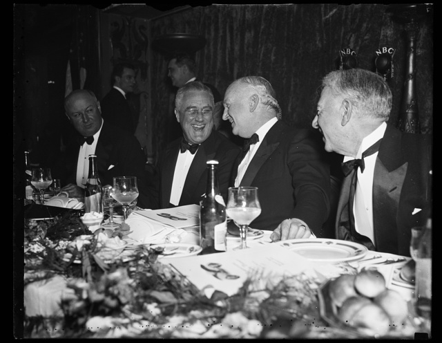PRESIDENT ENJOYS DEMOCRATIC VICTORY FEAST. WASHINGTON, D.C., MARCH 4. IN FINE FORM AND FLASHING THE TYPICAL 'ROOSEVELT' SMILE, PRESIDENT ROOSEVELT HEADED THE THOUSAND OR MORE LOYAL DEMOCRATS ATTENDING THE HUNDRED-DOLLAR-A-PLATE VICTORY FEAST TONIGHT AT THE MAYFLOWER HOTEL IN WASHINGTON. FIVE DOLLARS WORTH OF FOOD AND NINETY-FIVE DOLLARS TO THE DEMOCRATIC WAR CHEST WAS THE ORDER OF THE EVENING. THE CHIEF EXECUTIVE IS SHOWN WITH JOSEPH P. TUMULTY, FORMER SECRETARY TO THE LATE PRESIDENT WILSON, WHO WAS TOASTMASTER FOR THE DINNER. NOTE THE PRESIDENT'S RESEMBLANCE TO ANOTHER FAMOUS ROOSEVELT, THE LATE AND FORMER PRESIDENT THEODORE ROOSEVELT