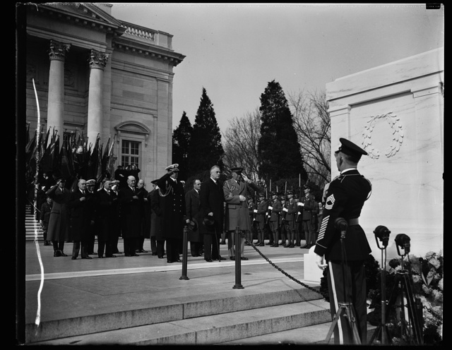 PRESIDENT PAYS TRIBUTE TO UNKNOWN SOLDIER. PRESIDENT ROOSEVELT TODAY LEAD THE NATION IN OBSERVING ARMISTICE DAY WHEN HE PLACED A WREATH ON THE TOMB OF THE UNKNOWN SOLDIER IN ARLINGTON. FLANKED BY HIS MILITARY AND NAVAL AIDES CAPT. WALTER B. WOODSON AND COLE. D. WATSON, PRESIDENT ROOSEVELT STOOD IN SILENCE AFTER THE TRIBUTE WAS PAID. IN THE REAR CAN BE SEEN SECRETARY OF WAR WOODRING, ASST. SECRETARY OF NAVY EDISON, ASST. SECRETARY OF WAR JOHNSON, AND U.S. CHIEF OF STAFF MALIN CRAIG
