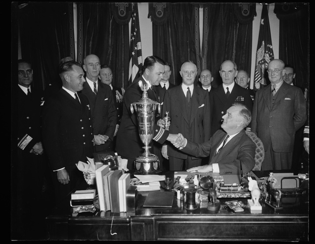 PRESIDENT PRESENTS SCHIFF TROPHY. WASHINGTON, D.C. DECEMBER 14. PRESIDENT ROOSEVELT TODAY PRESENTED THE SCHIFF TROPHY TO COMMANDER ROBERT FULLER, COMMANDING OFFICER OF VP SQUADRON SEVEN OF THE FLEET BASE FORCE AT SAN DIEGO. THE TROPHY IS AWARDED ANNUALLY TO THE NAVAL FLYING UNIT WHICH HAS THE BEST RECORD FOR THE YEAR IN SAFETY IN THE AIR. COMMANDER FULLER ON THE LEFT IS BEING CONGRATULATED BY THE PRESIDENT, WHILE HERBERT SCHIFF, DONOR OF THE TROPHY, AND CHIEF OF NAVAL OPERATIONS ADMIRAL WILLIAM LEAHY, LOOK ON