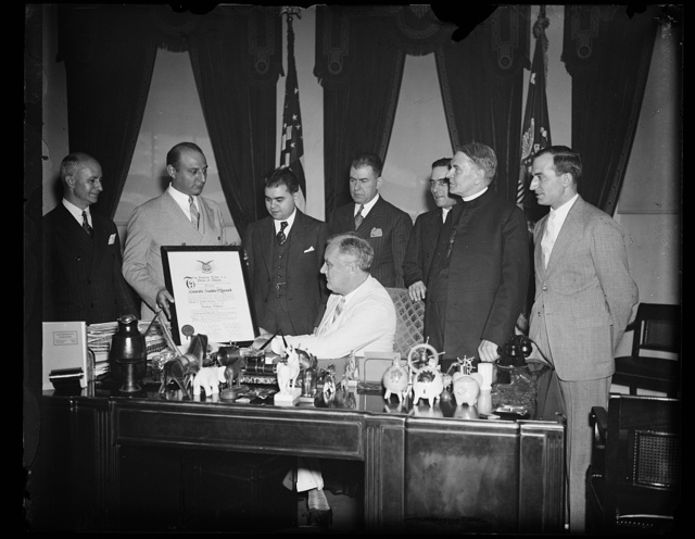 PRESIDENT RECEIVES FRATERNITY MEMBERSHIP SCROLL. WASHINGTON, D.C. JUNE 24. PRESIDENT ROOSEVELT TODAY RECEIVED A SCROLL REPRESENTING HIS MEMBERSHIP IN THE GREEK ORDER OF AHEPA. HE WAS INITIATED INTO THE ORDER MARCH 11, 1931, WHEN GOVERNOR OF NEW YORK. THE GREEK EDUCATIONAL ASSOCIATION MADE THE PRESENTATION THROUGHT ARTHUR G. SYRAN, NEW YORK, PRESIDENT. IN THE PHOTOGRAPH, L TO R: JOHN DOUNOUCOS, ARTHUR G. SYRAN, PETER VOUCHELAS, PRESIDENT ROOSEVELT, CONSTANTINE G. ECONOMON, EL POLITES, REV. THOMAS J. LACEY, AND THOMAS PALEDES