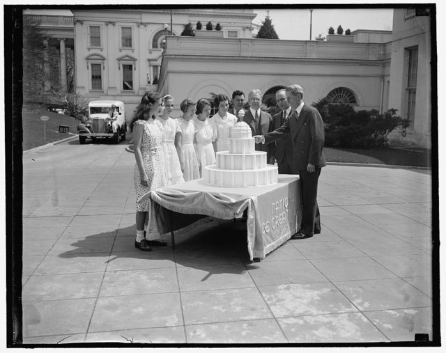 """President receives ice cream. Washington, D.C., April 17. Sec. to the President Marvin Mcintyre received a huge ice cream cake from the International Association of Ice Cream Manufacturers at the White House today. This is for """"ice cream week"""" for the nation from April 18th to April 24th. Left to right: Patricia Spellacy, age 13; Caroline Martin, age 12; Jean Engleback, age 13; Virginia Moeller, age 13; Robt. O. Ribben, Secretary to the above organization; George L. Smith; Ernest H. Daniel; and Marvin H. McIntyre Secretary to the President who received the cake for the president, 4/17/1937"""