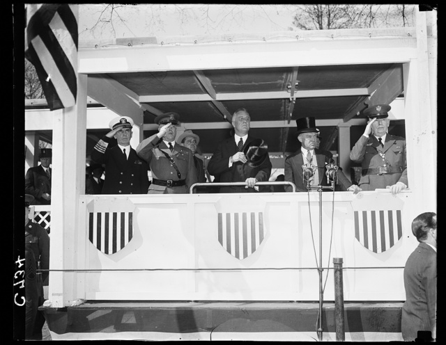 PRESIDENT REVIEWS ARMY DAY PARADE. WASHINGTON, D.C. APRIL 6. PRESIDENT ROOSEVELT WITH SECRETARY OF WAR HARRY H. WOODRING (RIGHT) AND GENERAL MALIN H. CRAIG, U.S. CHIEF OF STAFF; REVIEWING THE ARMY DAY PARADE IN THE CAPITAL IN OBSERVANCE OF THE TWENTIETH TWENTIETH ANNIVERSARY OF AMERICA'S ENTRANCE INTO THE WORLD WAR. EVERYBODY WAS IN 'SALUTE' IN THIS PICTURE BUT THE SECRETARY OF WAR