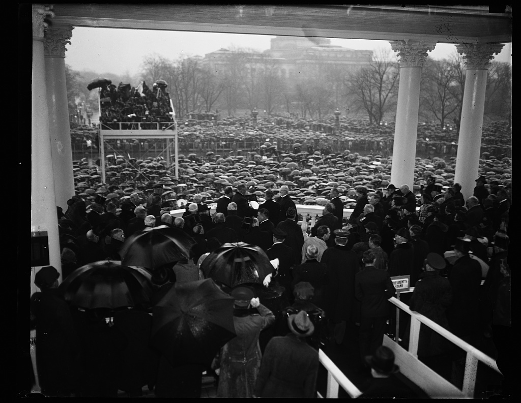 PRESIDENT TAKES THE OATH. REFUSING TO HAVE THE CEREMONIES MOVED INDOORS, PRESIDENT ROOSEVELT IS SHOWN BEING ADMINISTERED HIS SECOND OATH OF OFFICE BY CHIEF JUSTICE CHARLES EVANS HUGHES. THOUSANDS BRAVED THE HEAVY DOWNPOUR TO WITNESS THE CEREMONY