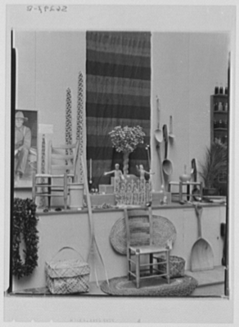 Rural arts exhibition held under the auspices of the Farm Security Administration (FSA) in the patio of the U.S. Department of Agriculture building. Left: photograph of chairmaker by Doris Ulmann; chair, Kentucky; basket, Puerto Rico, Virgin Islands; wooden chains made from one single piece of wood twenty feet long, Iowa; Right: basket, Hawaii; shovel and pitchfork, Connecticut; rawhide bottom chair, Texas; Garden of Eden carved by New Mexico Indians; wall hanging, WPA (Works Progress Administration),