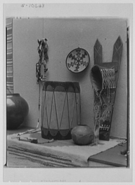 Rural arts exhibition held under the auspices of the Farm Security Administration (FSA) in the patio of the U.S. Department of Agriculture building. Handspun and woven rug from Colorado; beaded bridle and beaded papoose carrier made by Sioux Indians; small pottery and corn storage jar, drum and basket made by Indians of the Southwest