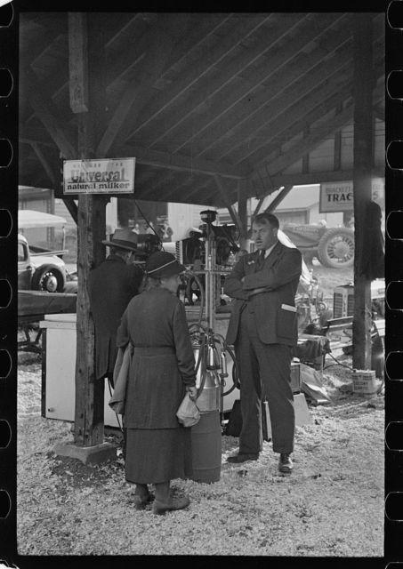 Salesman explaining new milking machine, State Fair, Rutland, Vermont