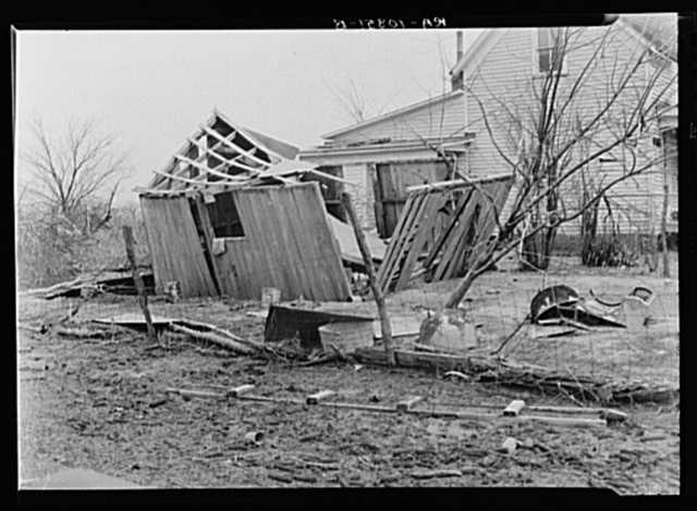 Shattered outbuilding and debris in an Indiana farmyard. 1937 flood