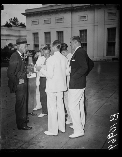 Tenders resignation to president. Washington, D.C., Aug. 11. Lyle T. Alverson, Chairman of the National Emergency Council, leaving the White House today after submitting his resignation to President Roosevelt. After the President accepted the position for a limited time and he was anxious to return to New York to his private business. Alverson, extreme left, talking to newspapermen