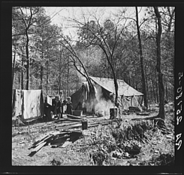 Tent occupied by sharecropper family now living in a migrant camp near Birmingham, Alabama. Note water supply at right
