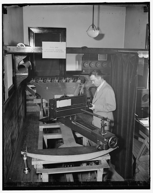 Testing airplanes lenses used in map making. Washington, D.C., May 6. Dr. F.E. Washer of the U.S. Bureau of Standards testing the lens for the airplane cameras that are used by the Army and Navy. There are lights in the rear of the columnmeters and exposures are made on the photographic plate in front of the doctor. The lens are tested for distortion, focal length, and definition. This work must be very exacting as a small error would make an error of many miles on the maps made by the aerial cameras, 5/6/1937
