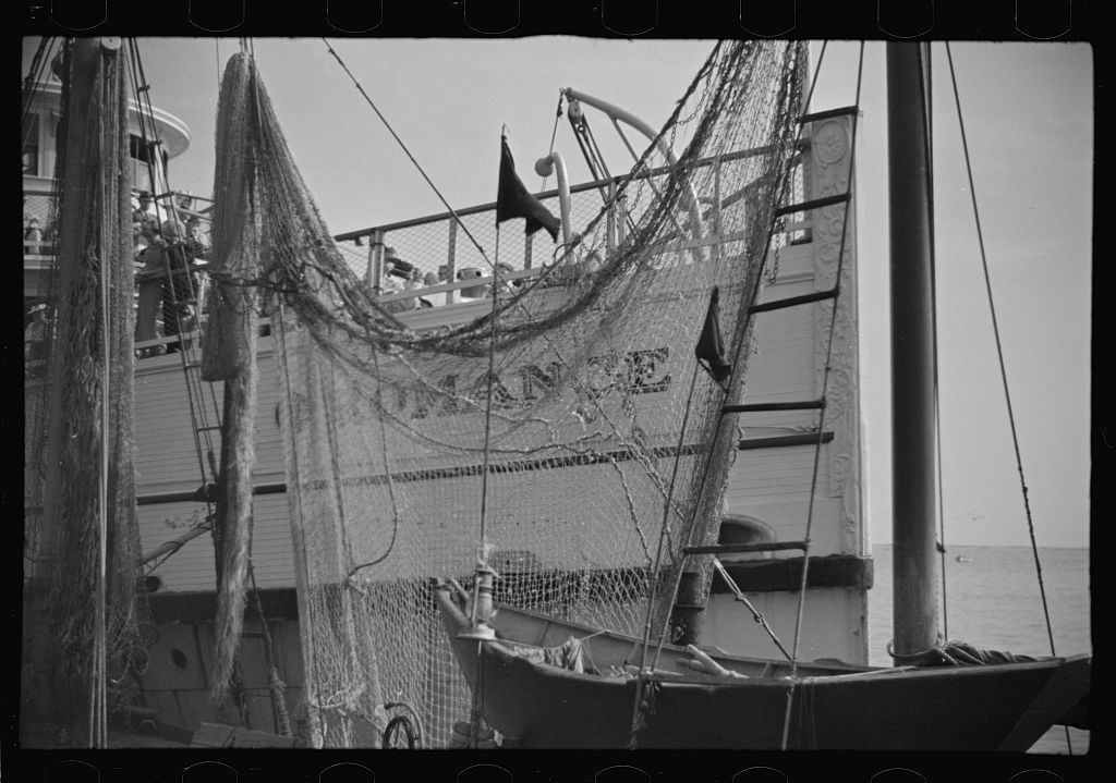 "The economy of a town: fishing and the tourist trade. A fishing boat in front of the S.S. ""Romance,"" a tourist boat which used to ply between Boston and Provincetown and has since sunk in Boston Harbor. Provincetown, Massachusetts"