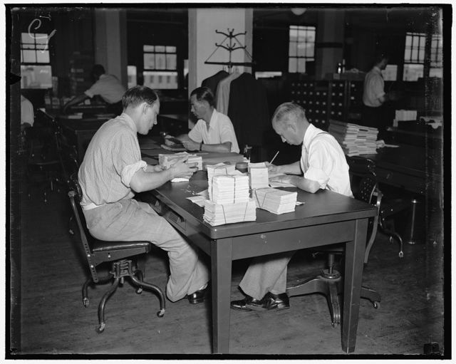 """There is nothing """"hit or miss"""" about the handling of account applications in the Social Security Board Records Office. To facilitate keeping a constant check on each, applications are grouped in blocks of 1,000, numbered in sequence, before they are started through the various operations necessary to set up an individual ledger account for every worker. The photograph above shows workers in the Records Office assembling applications in to blocks of 1,000."""