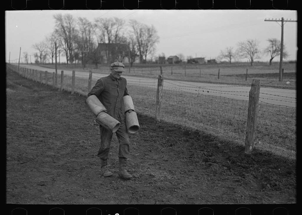 Tip Estes carrying tiles to load on a wagon, Fowler, Indiana