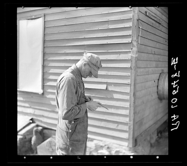 Tip Estes, forty-three year old hired man and father of nine children, whittling on a piece of wood. Near Fowler, Indiana