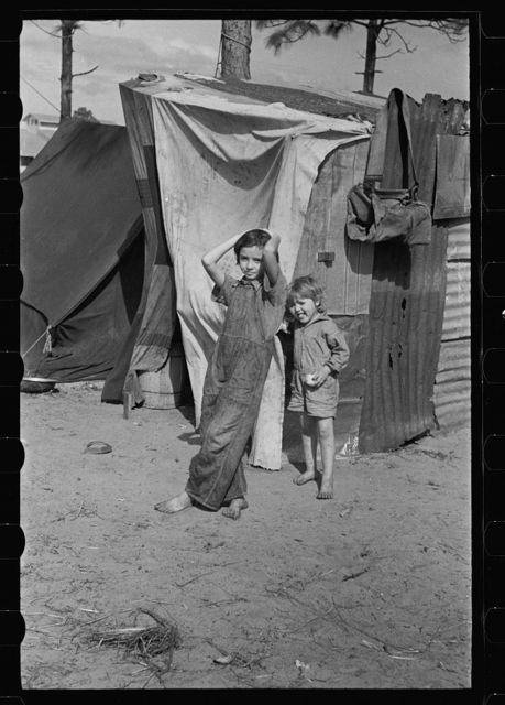 Two children of a migrant fruit worker from Tennessee, standing before their temporary home. This family of eight is camped in a field near the packinghouse at Winter Haven, Florida