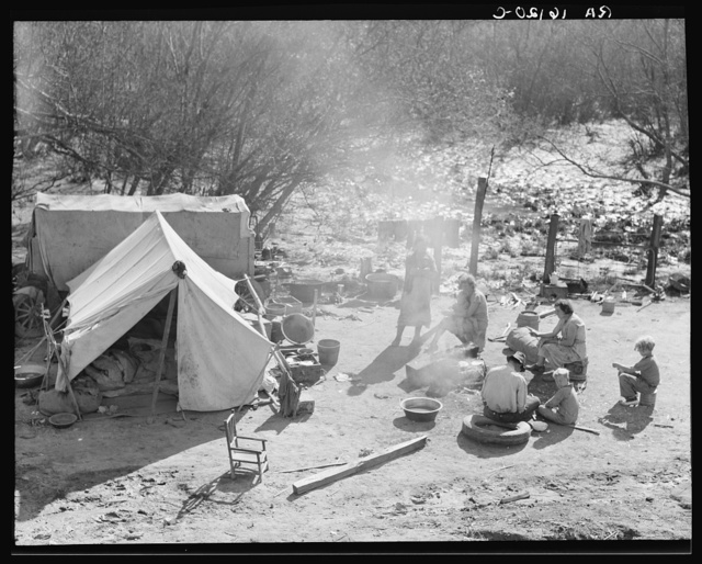 Two families, fifteen people, from Chickasaw, Oklahoma, camped by the roadside near Santa Maria, California. Heading for the pea harvest but stalled because they have no money to buy a trailer's license