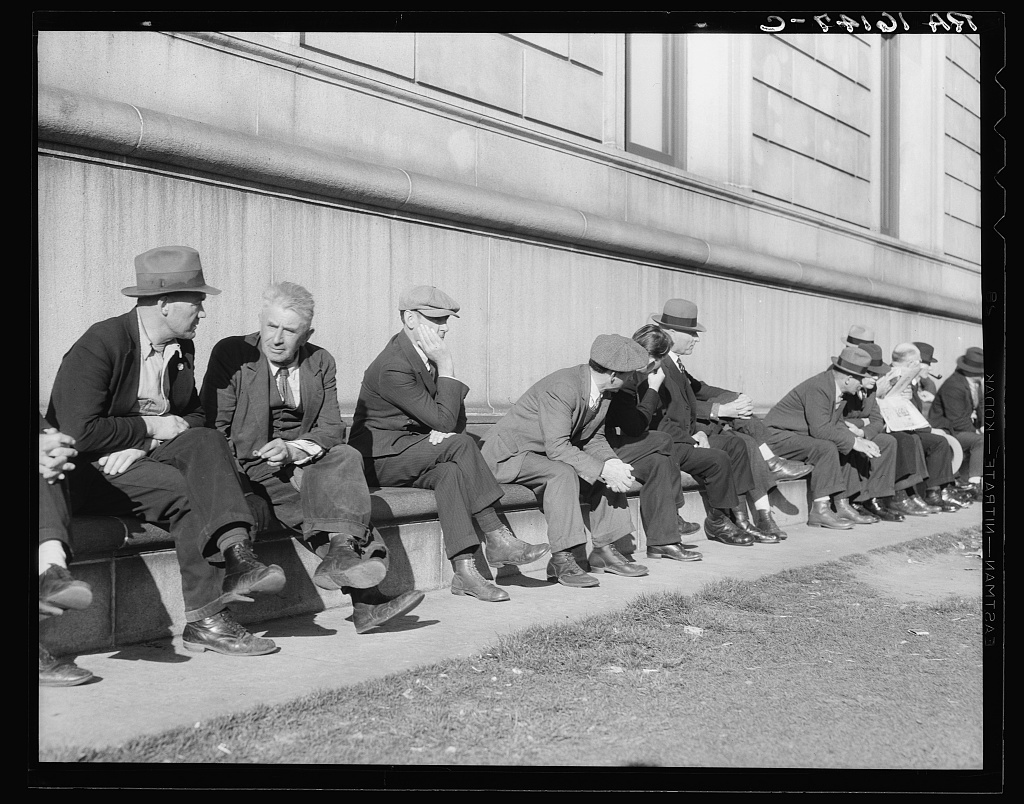 Unemployed men sitting on the sunny side of the San Francisco Public Library. California