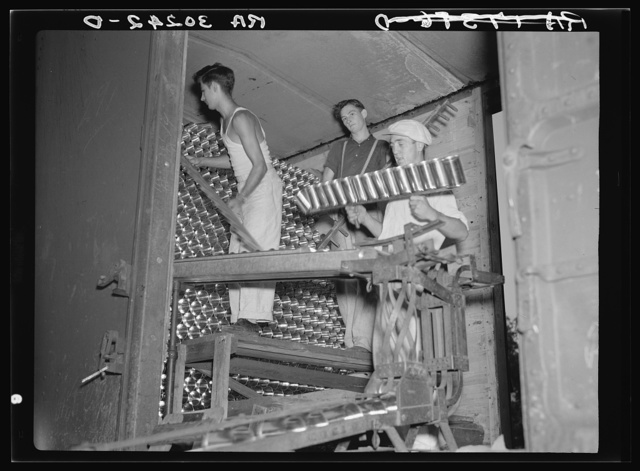 Unloading cans from boxcar. Canning factory, Sun Prairie, Wisconsin