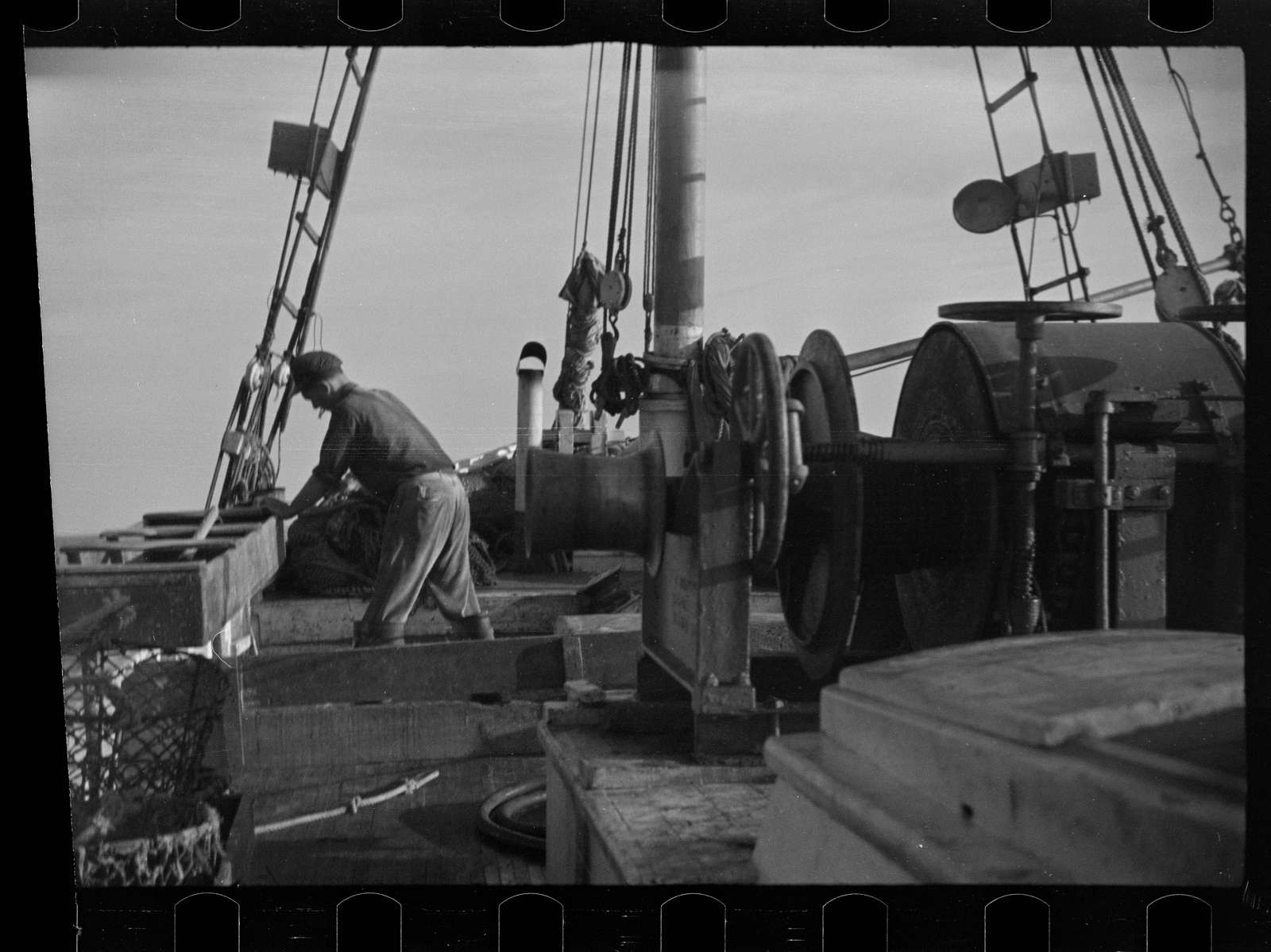 """Untitled photo, possibly related to: Aboard a trawler (locally called a dragger). The power-driven winch lets out the starboard net. While over fishing grounds one of two nets is constantly in the water, dragging along the bottom. Boats are powerful, diesel-engined, between forty and seventy-five feet long. Their unrestricted use has done much to cause the """"fish-famine"""" along this coast because nets bring up everything, fish, minnows and even spawn. Provincetown, Massachusetts"""