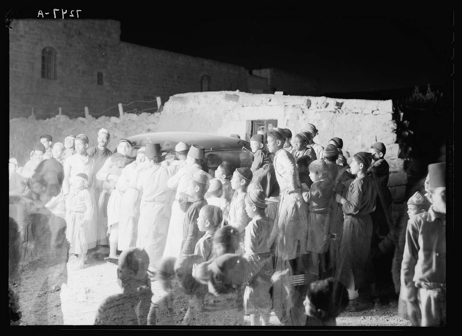 Villagers of el Khadder, listening in to radio of a passing car at night, Oct. 1937