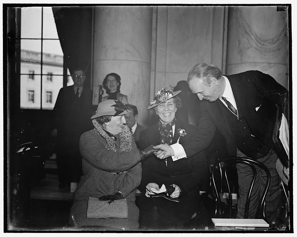 """Welcome ladies! Washington, D.C., March 19. The open hearing being by the Senate Judiciary Committee on the President's proposed Supreme Court plan is proving the """"hit"""" of the present congressional session, at least by the members of the fair sex. Here we see Senator Henry F. Ashurst, Chairman of the Committee, greeting Mrs. Joseph E. Davies, former wife of the American Ambassador to the Soviet, and her daughter Mrs. Millard Tydings, wife of the Maryland Senator, as they arrived to attend today's session, 3/19/1937"""