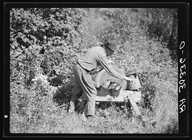 William Besson, old iron ore prospector, grinding an axe near Winton, Minnesota