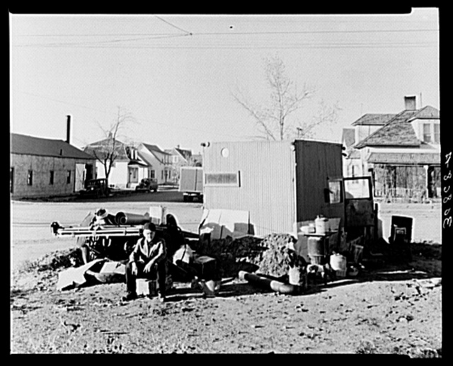 Williston, North Dakota. Theodore F. Jeffries, squatter on street corner of Williston, North Dakota. This is an old truck, bright red, with the body removed from the chassis which he is fixing up for his winter home having lost his home to the loan company. County FSA (Farm Security Administration) supervisor advises that he was recently yardmaster on the Great Northern Railroad and that at one time he was one of the best reporters on the New York Times. He is now a radical