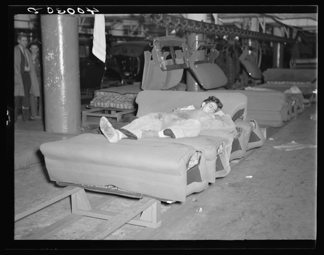 Young striker off sentry duty sleeping on assembly line of auto seats in Fisher body plant factory number three. Flint, Michigan