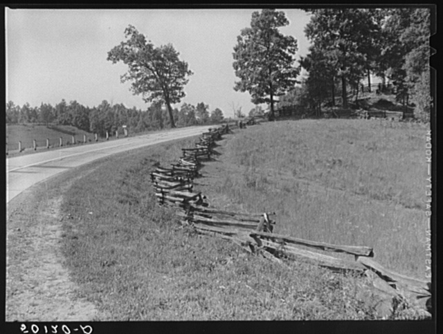 A new main highway with old rail (snake) fence at edge of field beside it. West Virginia