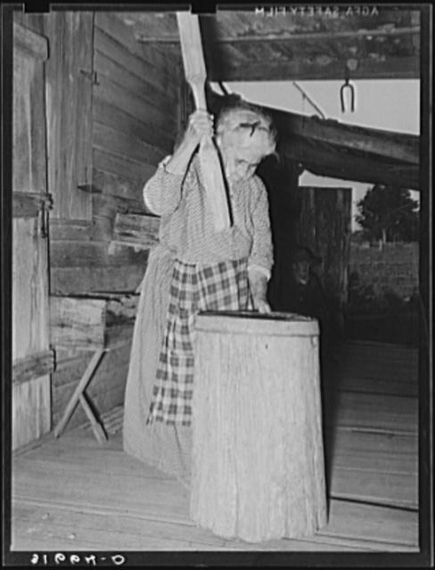 Aged Cajun woman using crude mortar and pestle in process of hulling rice. Near Crowley, Louisiana