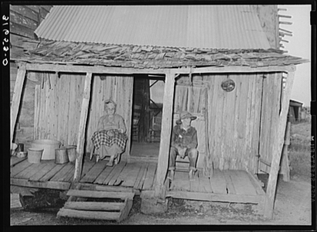 Aged couple sitting on front porch of farm home near Crowley, Louisiana