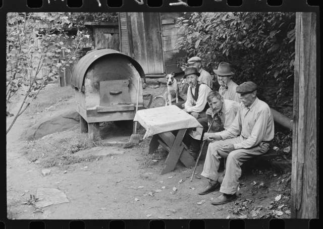 "Bohemian miners (coal loaders) unemployed since mechanization of mines. Jere, West Virginia. They live together in one house with a woman housekeeper. All on relief. Spend most of their time fighting about politics. Call their dog ""Hitler"" because he's so mean and nasty. To the left is an outdoor oven for baking bread. Abandoned mining town"