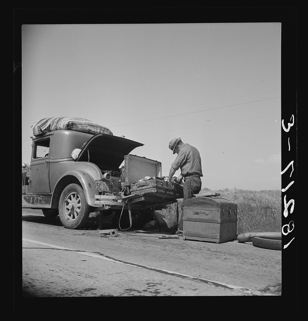 """Car trouble on west side, Highway no. 33. In San Joaquin Valley. Formerly a California cowhand and roving laborer, now with wife, he follows the fruit. """"My uncle homesteaded here sixty years ago. I'm lower on money than at any time"""""""
