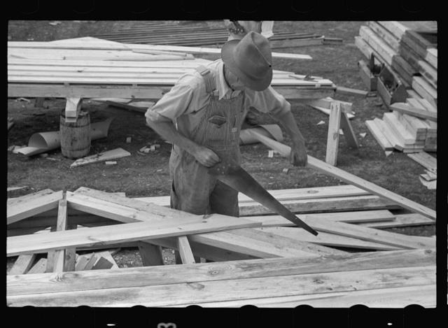 Carpenter working on gable of prefabricated house, Roanoke Farms, North Carolina