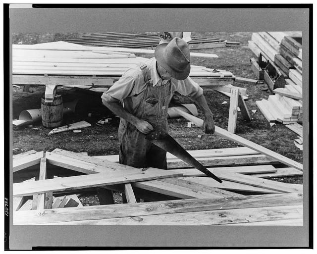 Carpenter working on gable of prefabricated house, Roanoke Farms, North Carolina