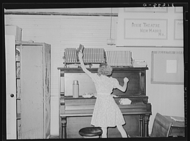 Child removing book from shelf in school room. Southeast Missouri Farms