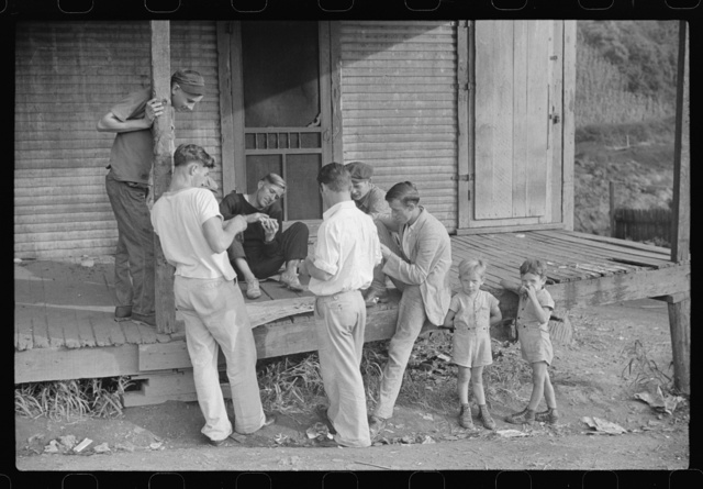 Coal miners card gambling Saturday afternoon on porch of company store, Chaplin, West Virginia