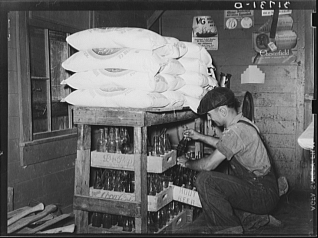 Corner of grocery store with man taking bottled drinks from supplies to fill ice box. Near New Iberia, Louisiana