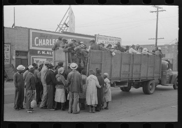 Cotton pickers boarding truck to take them to cotton fields, Pine Bluff, Arkansas